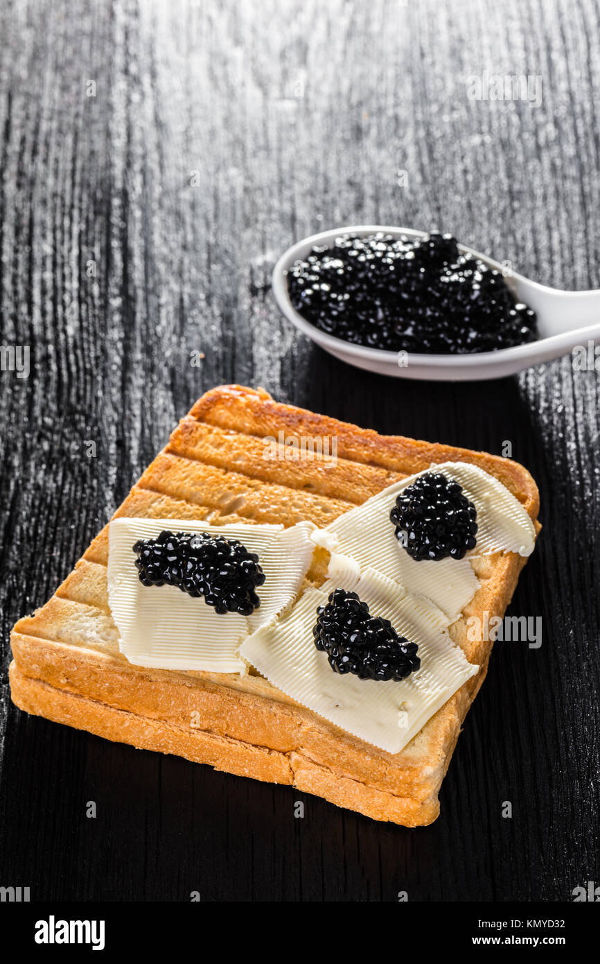 Toast with butter and caviar black wooden background - Stock Image