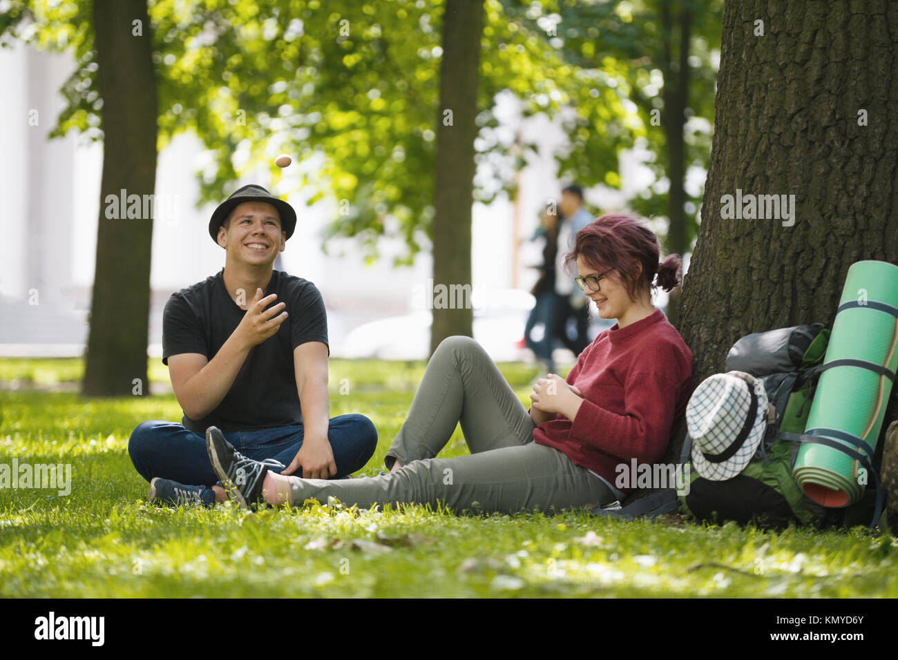 Young couple tourists with backpacks have rest in the park - Stock Image
