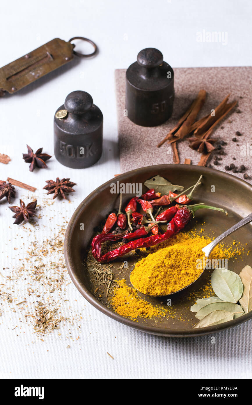 Spices Tumeric And Dry Reh Hot Chili Peppers On Metal Plate, Srved Over  White Tablecloth With Vintage Weight.