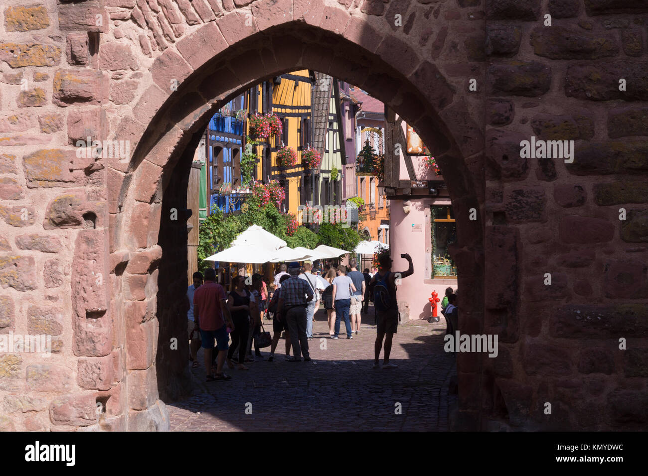 Tourists passing through the Obertor (upper gate) into the 16th century town of Riquewihr on the popular Route des - Stock Image