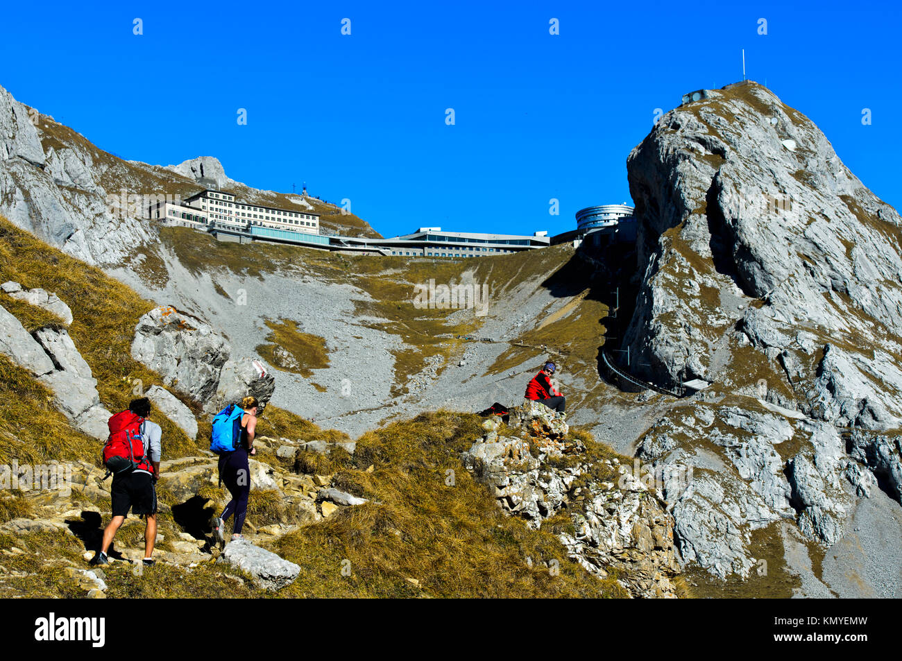 Hikers in the Pilatus massif, behind hotels Pilatus Kulm and Pilatus Bellevue, peak Esel, Alpnachstad, Switzerland - Stock Image