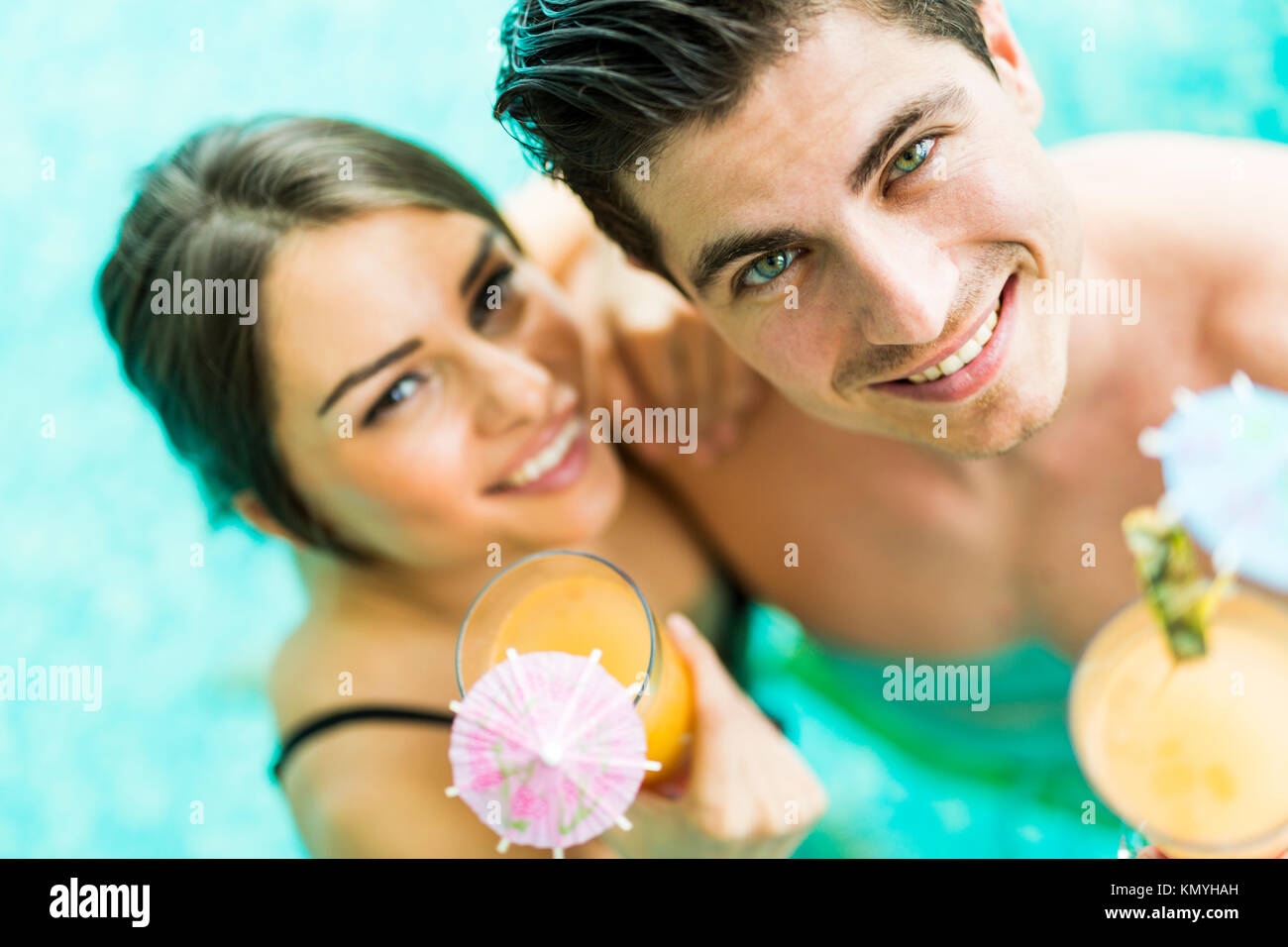 Portrait of a couple smiling and drinking a cocktail in a pool - Stock Image
