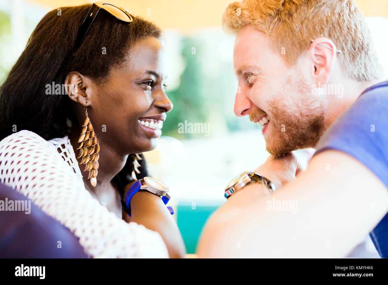 Romantic couple smiling while looking into each others eyes - Stock Image
