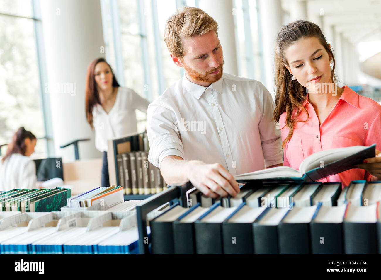 Two students reading and studying in library - Stock Image