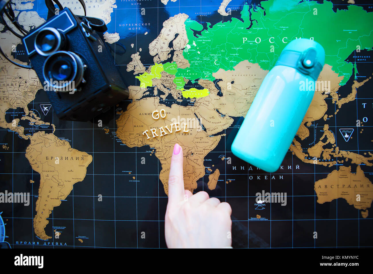 Map of the world in Russian. The finger of the girl points to different corners of the world - Stock Image