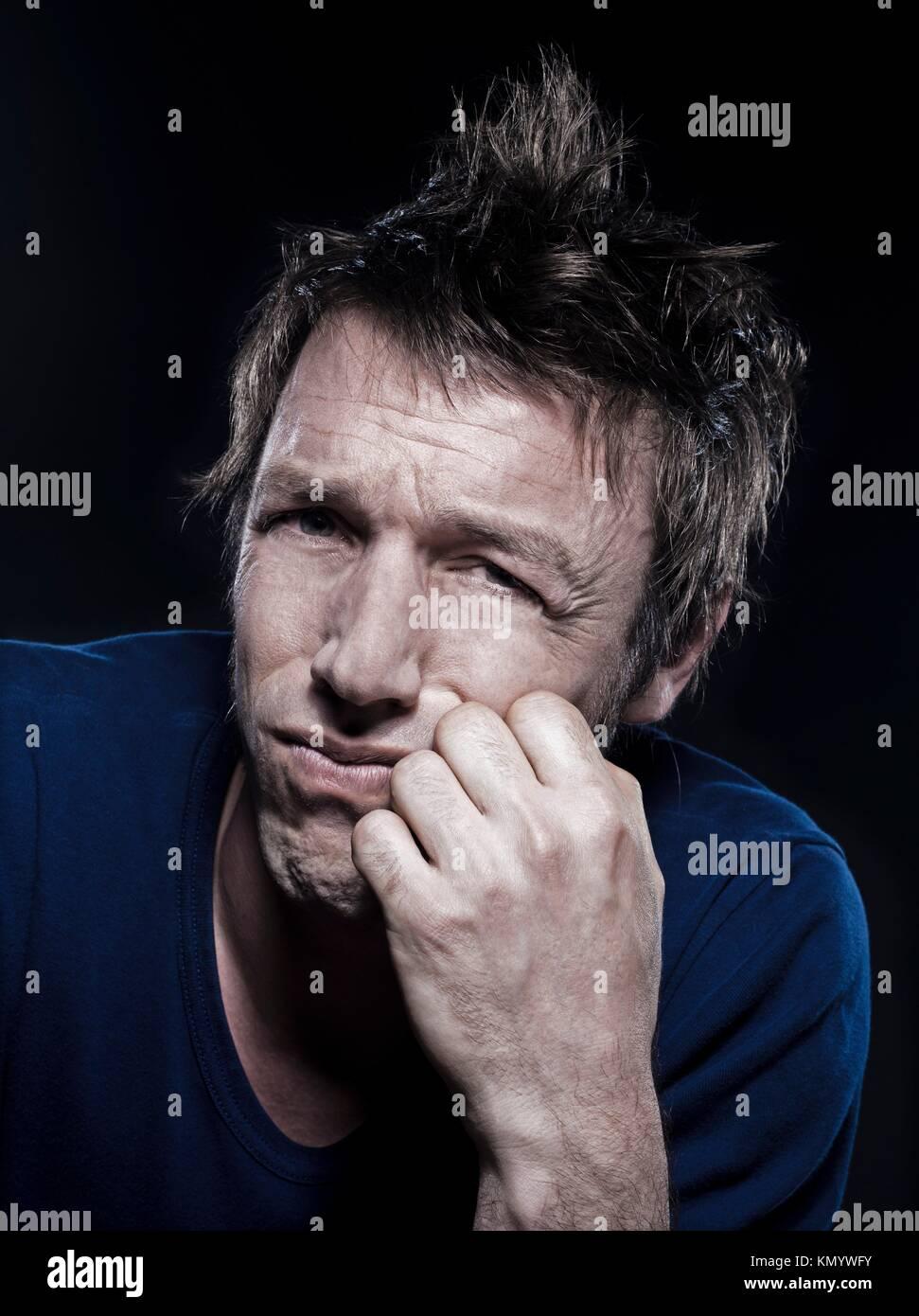 studio portrait on black background of a funny expressive caucasian man puckering sad sullen - Stock Image
