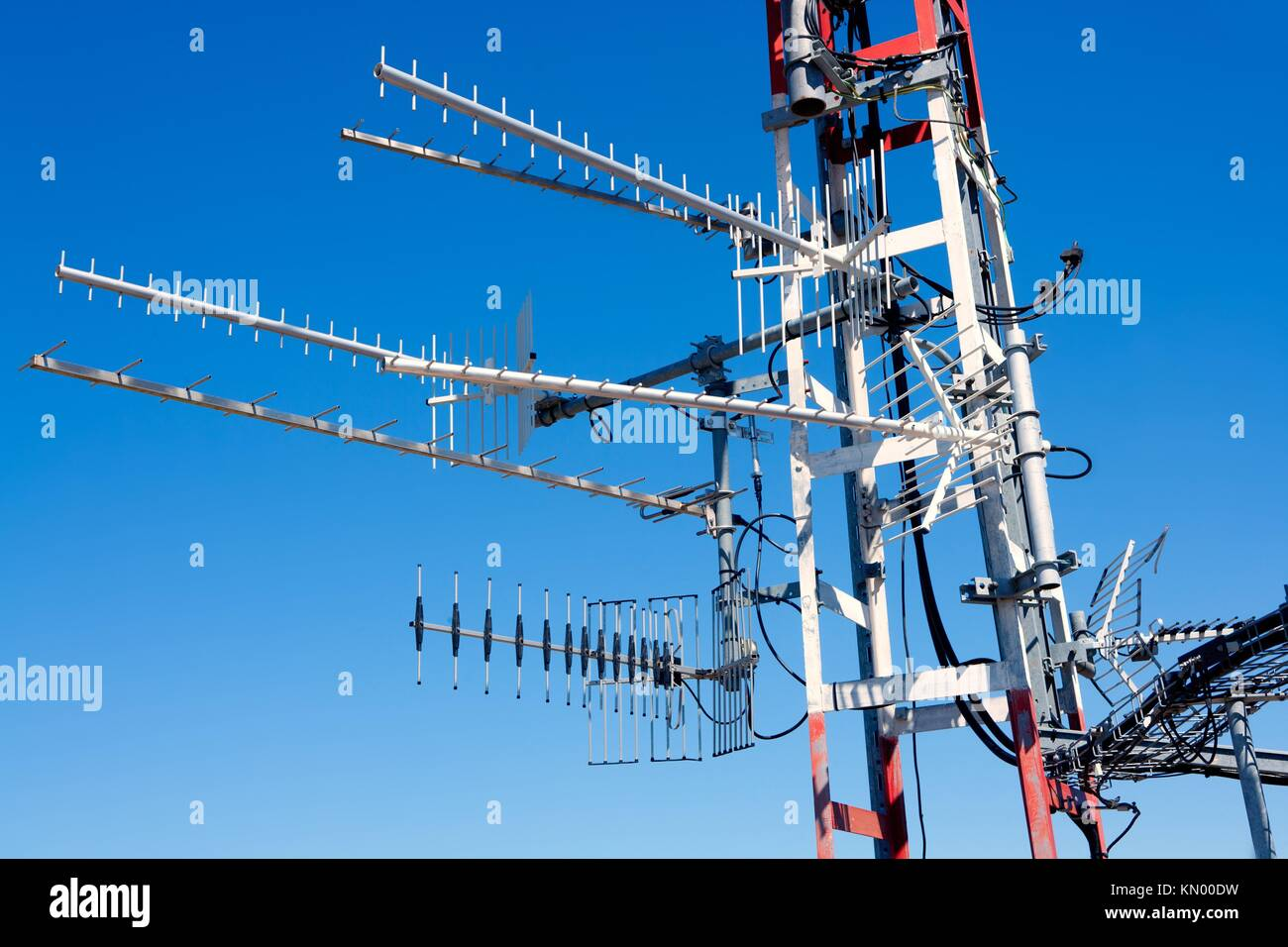 Antenna repeater messy mast with tv radio and telephone Stock Photo