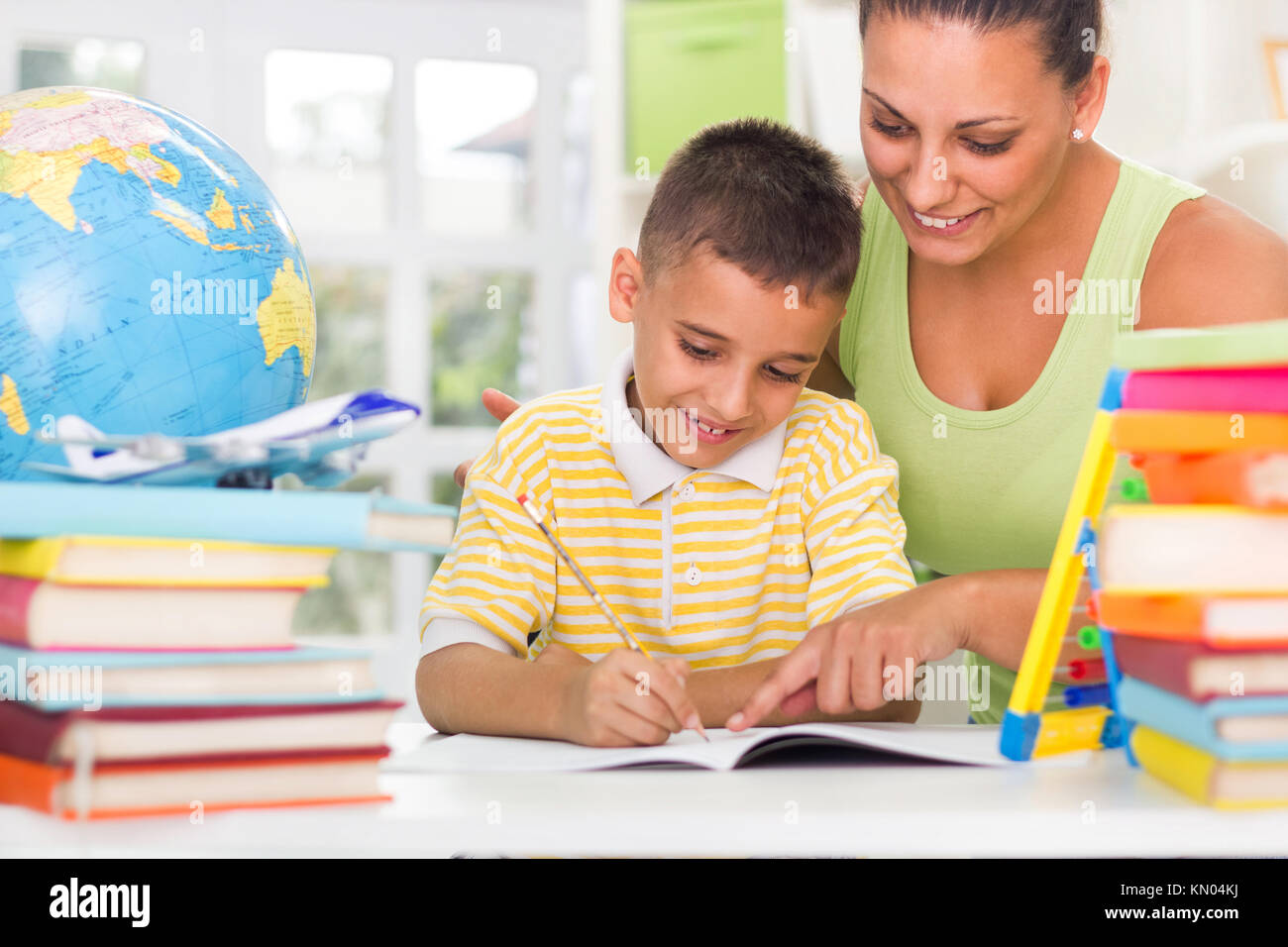 Mother helping her son to prepare for written assignment - Stock Image