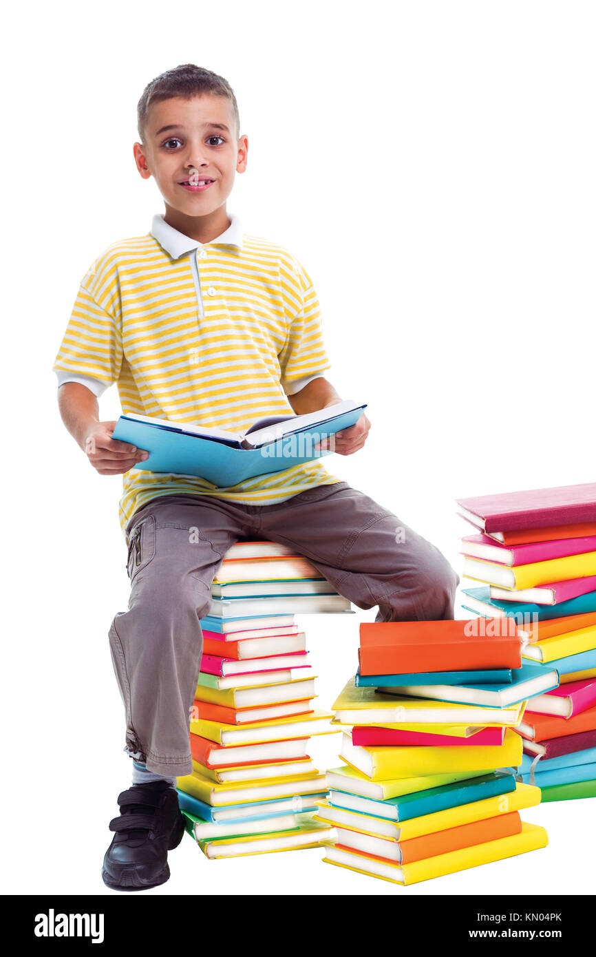 boy sitting on a pile of books and holding one book in his hands - Stock Image