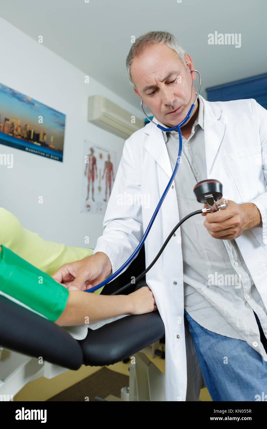Doctor concentrating on blood pressure gauge - Stock Image