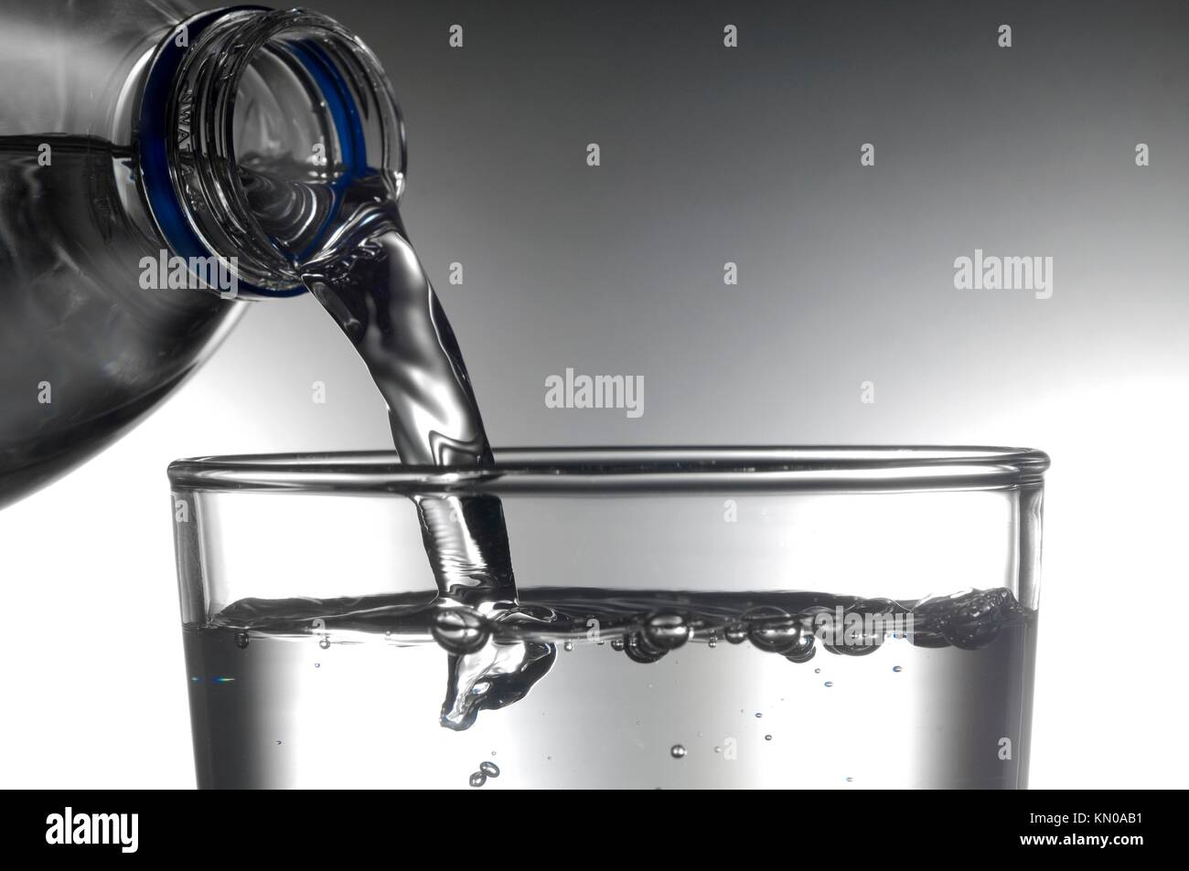 serving water bottle in a glass - Stock Image