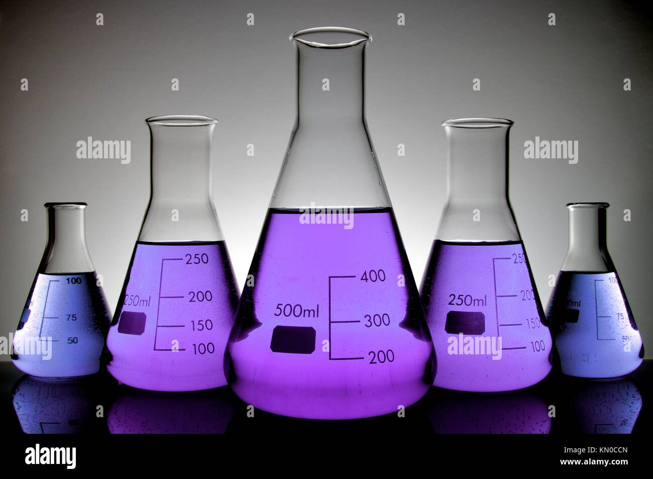 five vials of purple liquid conical laboratory on a white background Stock Photo