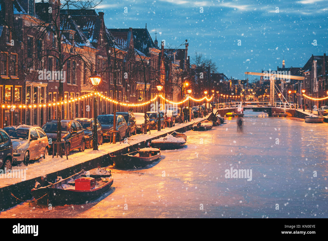 Winter scene in Alkmaar Netherlands with natural ice and falling snow - Stock Image