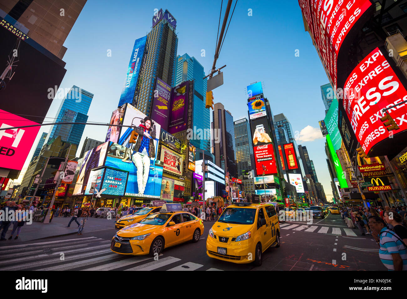 NEW YORK CITY - AUGUST 23, 2017: Bright neon signage flashes over crowds and taxi traffic zooming past Times Square, - Stock Image