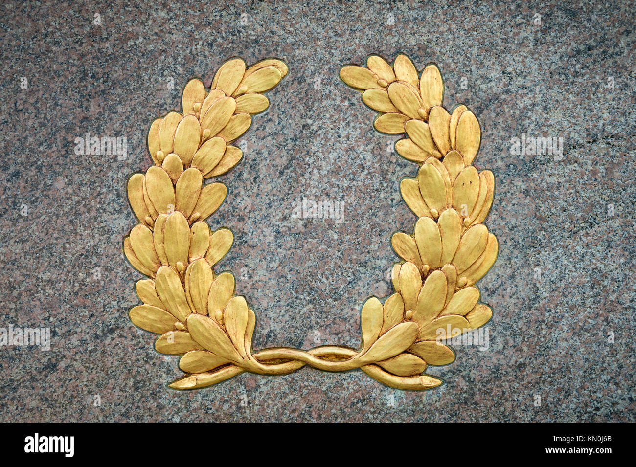 Classic laurel wreath symbol with vintage gold leaf detail on textured raised relief against a smooth gray stone - Stock Image