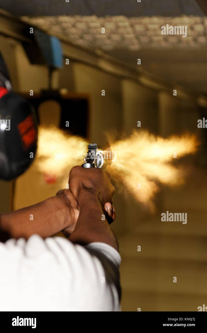 A picture taken over the shoulder of a young man firing a gun at a shooting range in the precise moment of the muzzle - Stock Image