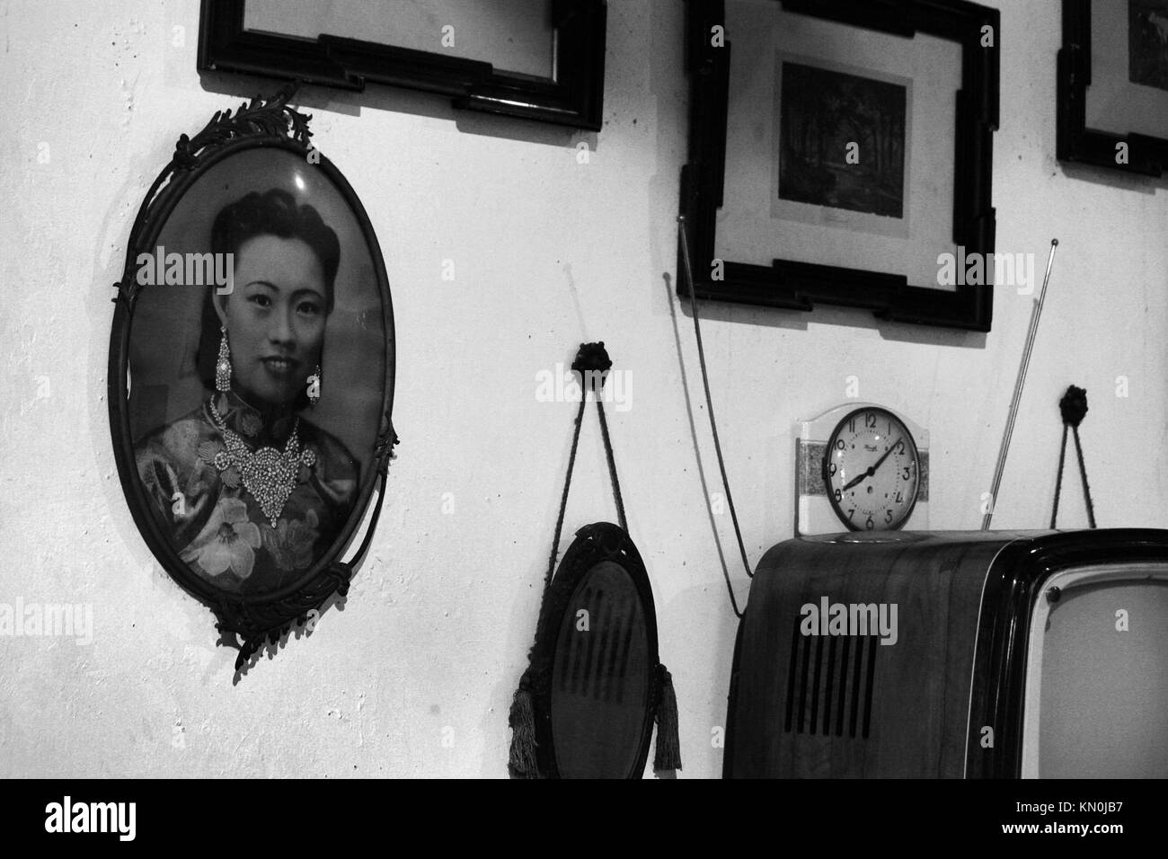A wall display of historical and family framed portraits and mirror reflections in the Sun Yat-Sen Museum Penang - Stock Image