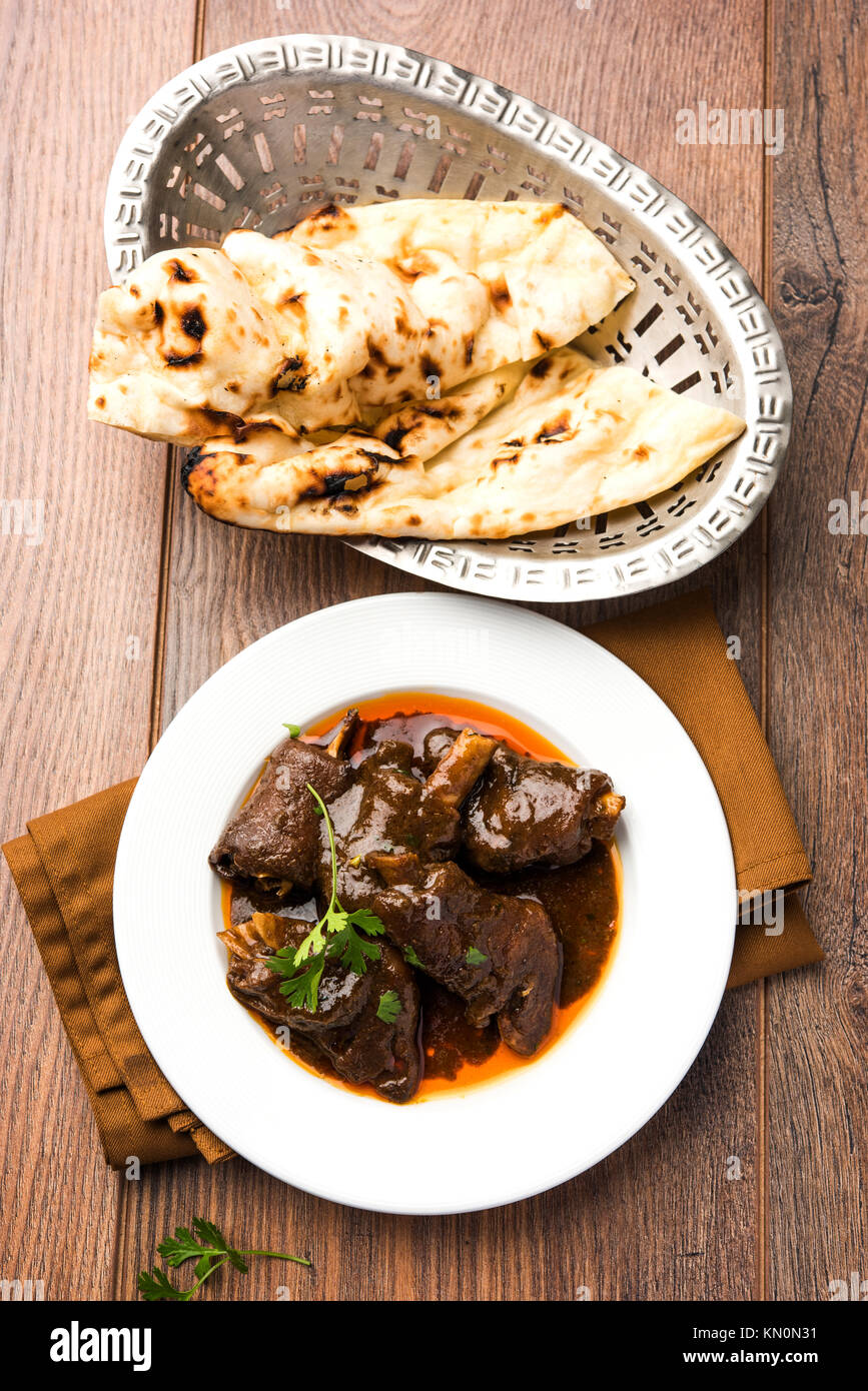 lamb shank or mutton or gosht paya or khoor curry served with indian bread or roti or naan - Stock Image