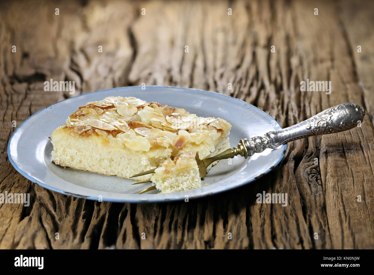 Traditional North German Butterkuchen (butter cake) on old enamel plate. - Stock Image