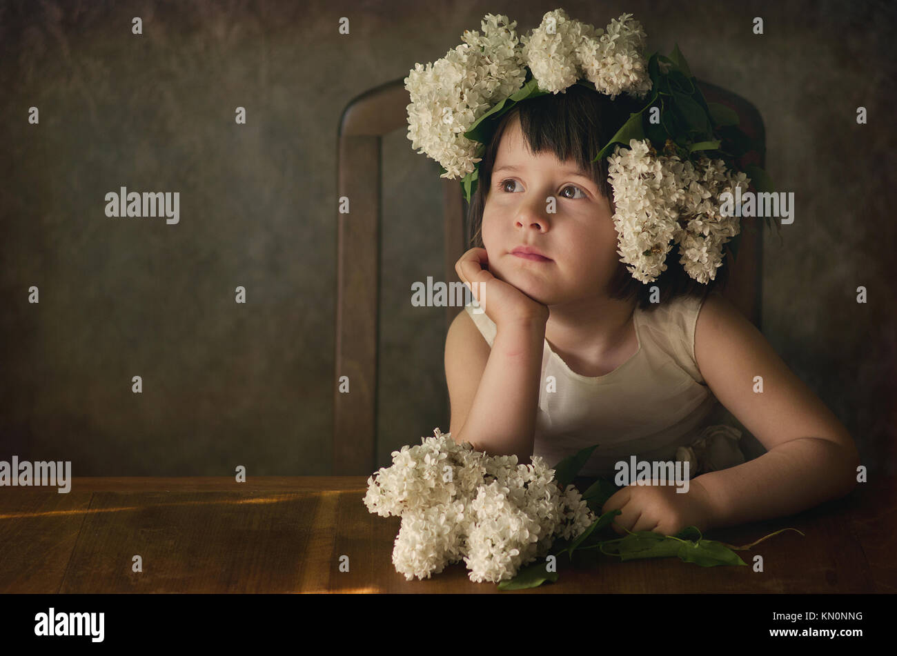 Studio portrait of beautiful girl 2-4 years with lilac flower garland on her head. Dreamy mood, creative look. - Stock Image