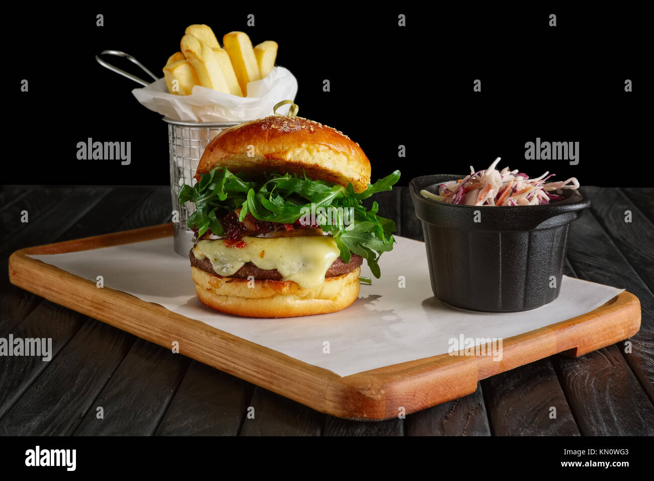 Juicy beef burger with lingonberry sauce, melted cheese, arugula served with fried potato and red cabbage Stock Photo