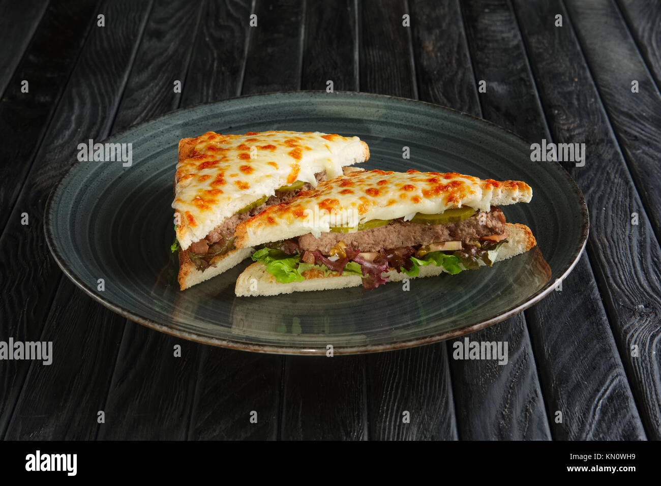 Club sandwich with meat, pickled cucumber , salad and melted cheese - Stock Image