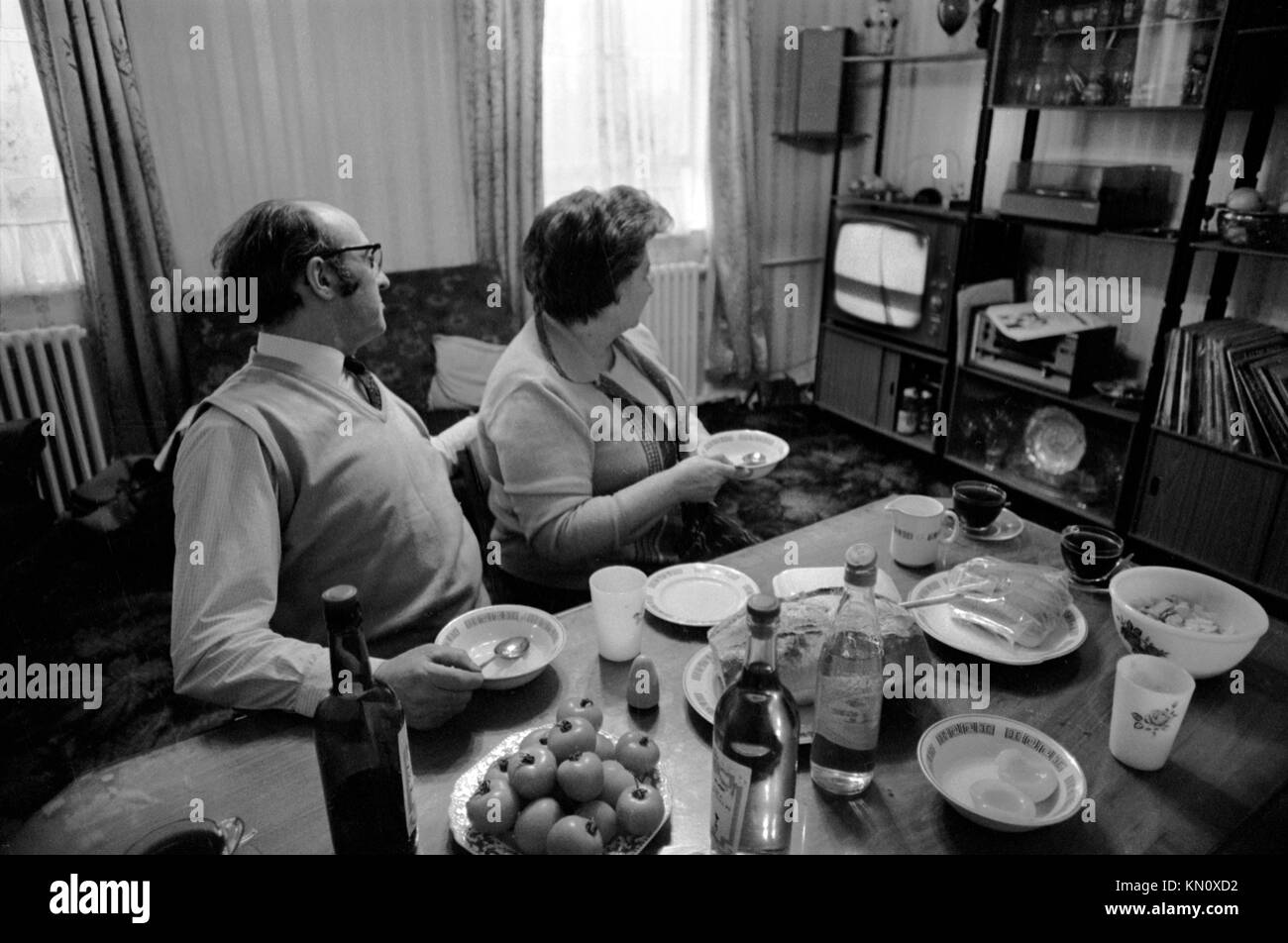 Watching TV television while eating dinner at dining room table,  interior of flat north London 1970s UK HOMER SYKES - Stock Image