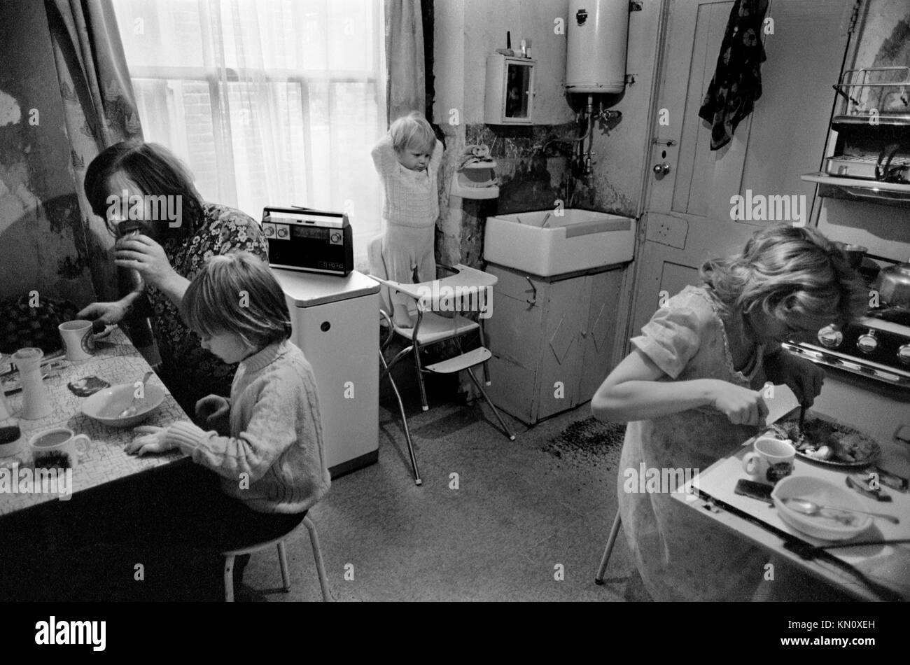 Poverty uk 1970s slum housing , kitchen doubles as bathroom. Family eating together. Ascot gas water heater on the - Stock Image