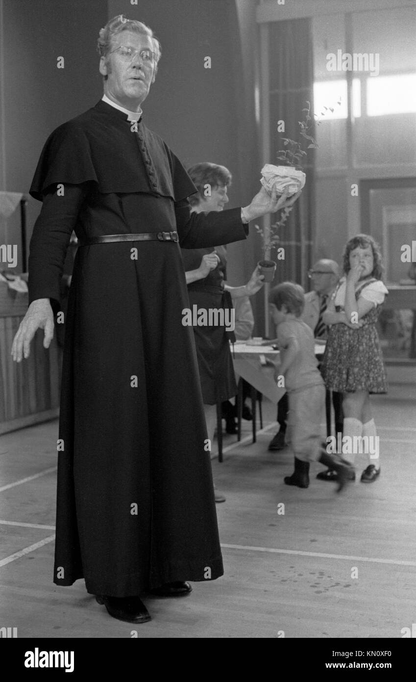 Village fete 1970s England, rained off inside church hall, the vicar giving out the prizes. 770s UK HOMER SYKES - Stock Image