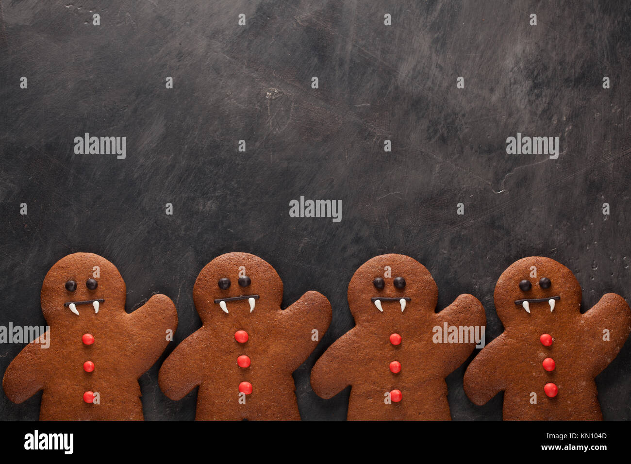 Homemade gingerbread cookies for Halloween in the form of gingerbread men vampire on dark concrete background with - Stock Image