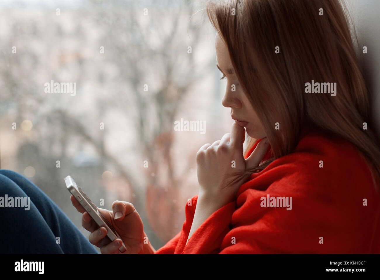 Portrait of a young girl reading a message on a telephon sitting by the window. - Stock Image