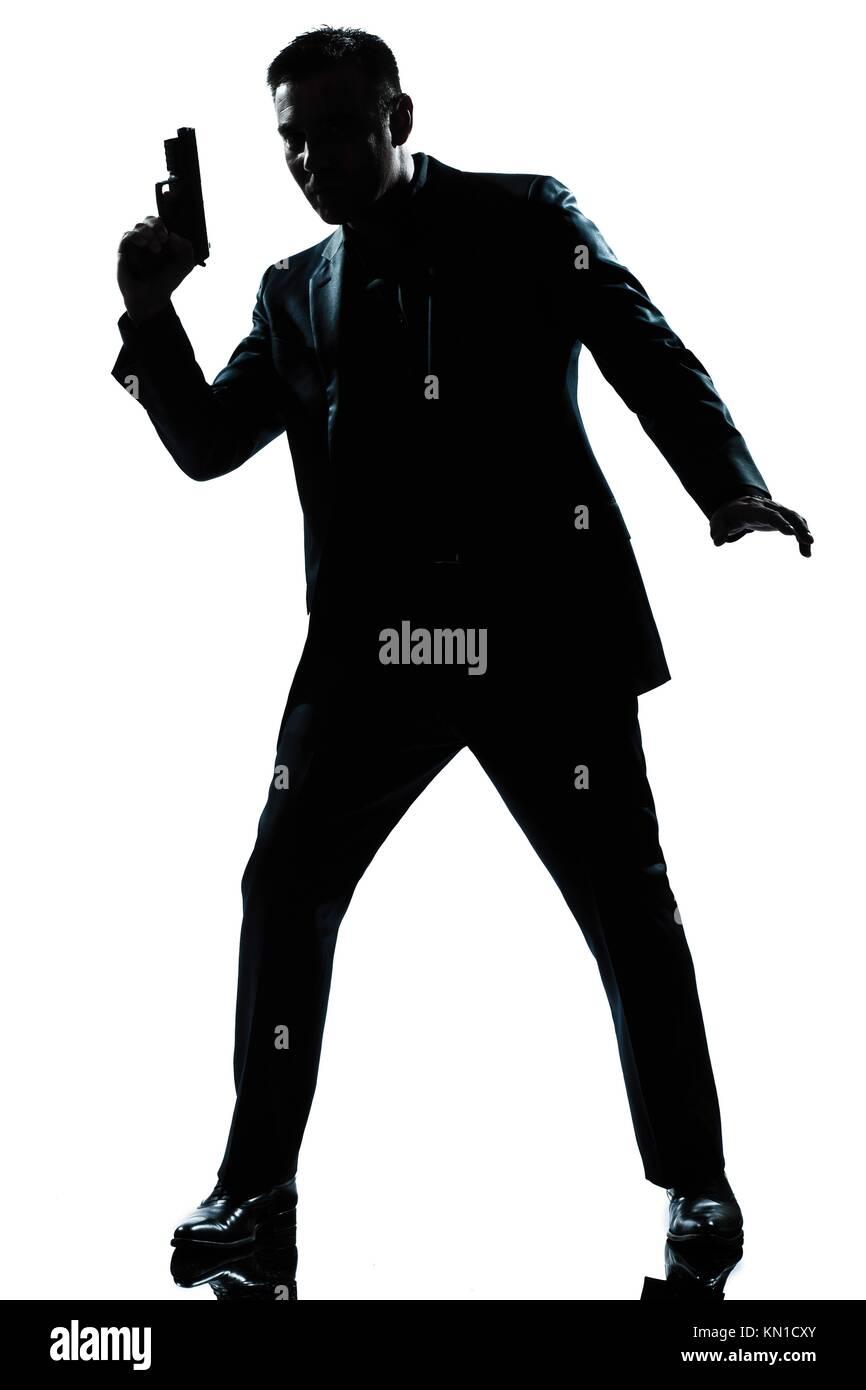 one caucasian spy criminal policeman detective man holding gun full length silhouette in studio isolated white background - Stock Image