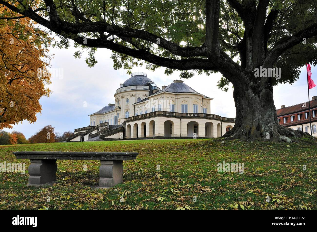 autumnal foresight of the famous castle located in a park in surroundings of the city, to the fore a bench and centuries Stock Photo