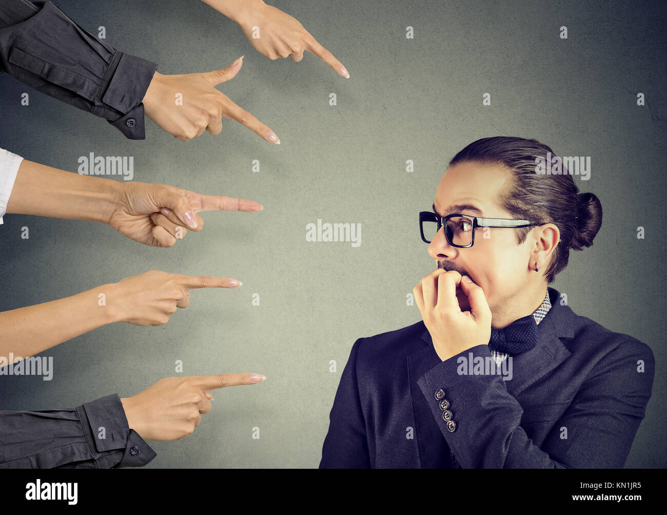 Anxious man scared of being judged by different people. Concept of accusation of guilty guy. Negative emotions face - Stock Image