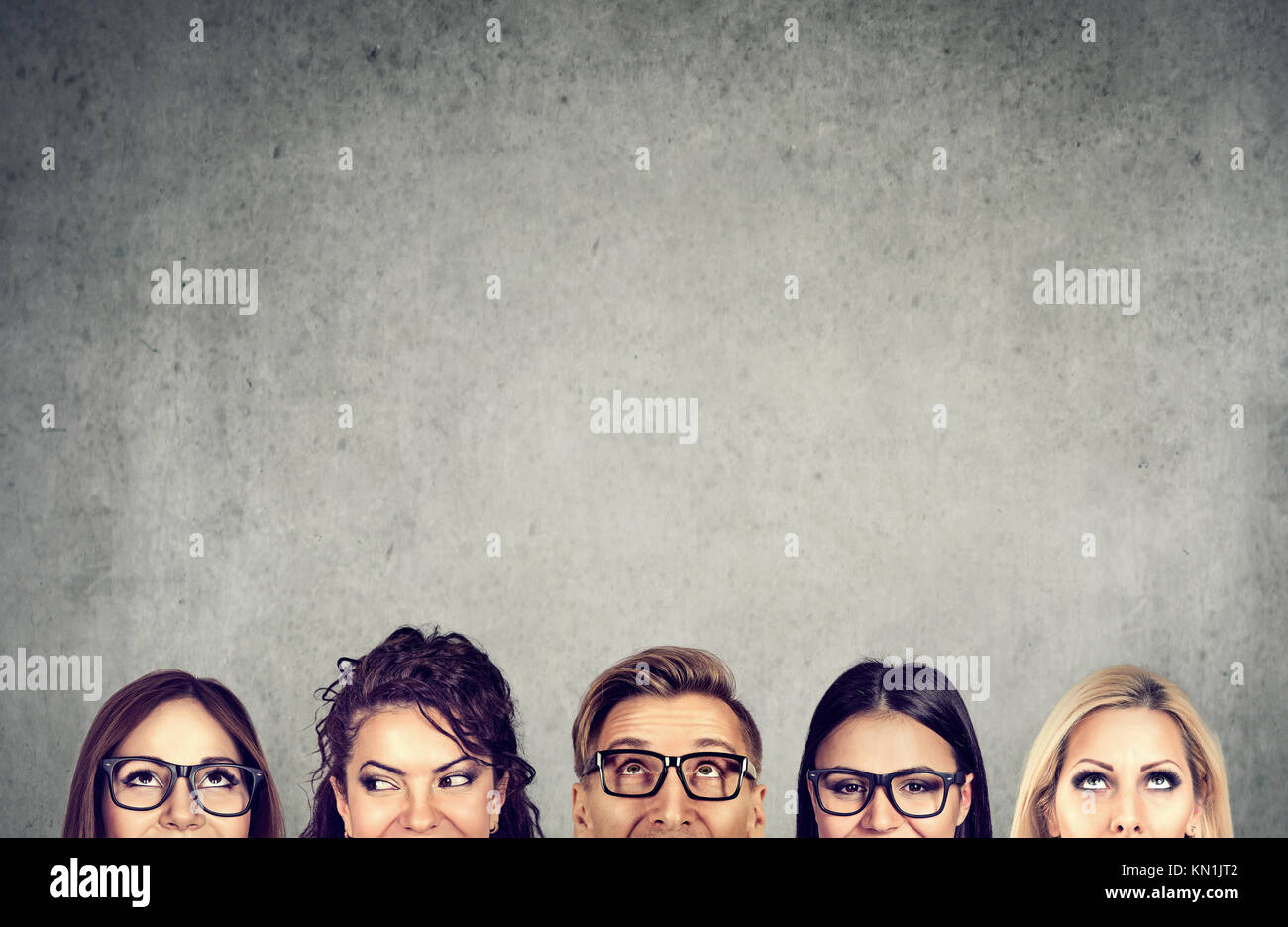 Closeup of young people heads standing near a gray concrete wall. A diverse business team and brainstorming concept - Stock Image