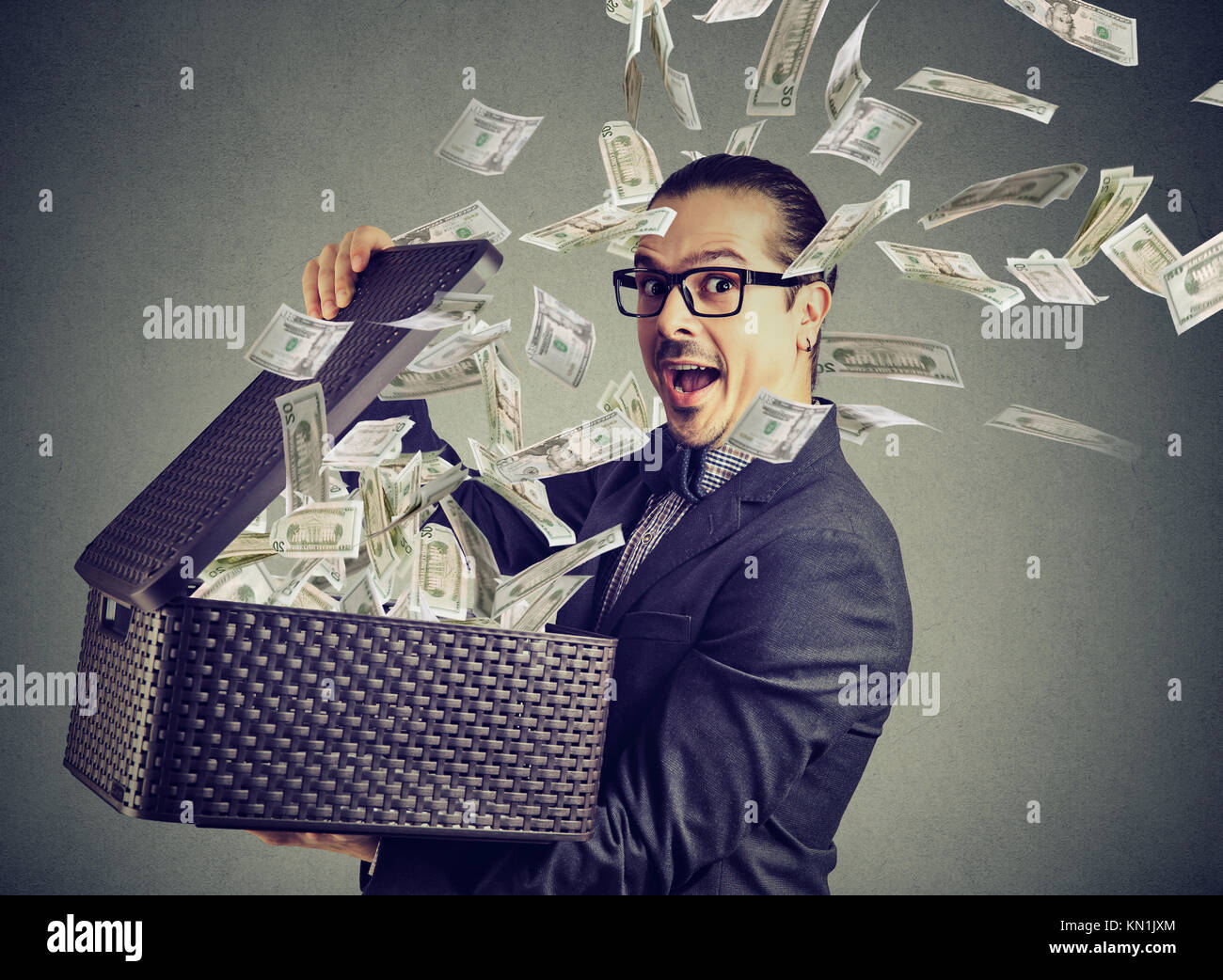 Excited successful business man opening a box with money flying out away - Stock Image