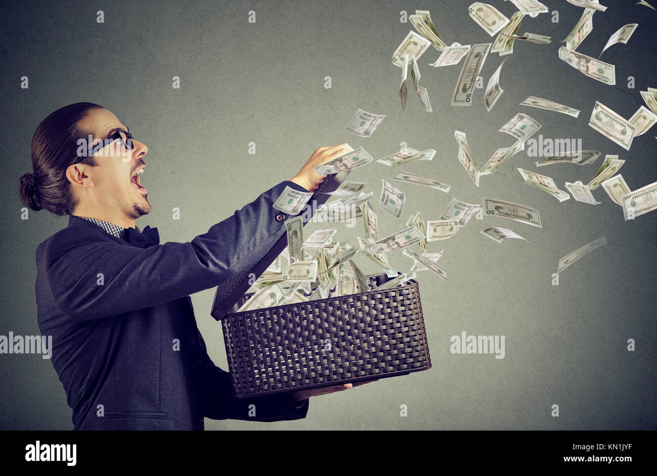 Excited business man opening an box letting dollar banknotes to fly away - Stock Image