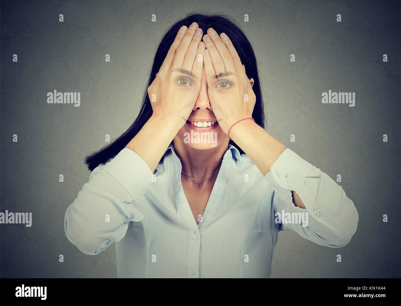 Portrait of a smiling woman covering her eyes - Stock Image