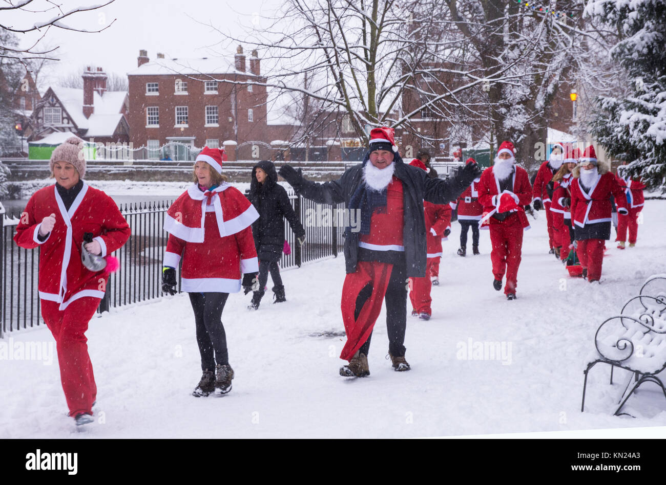 Lichfield, UK. 10th Dec, 2017. People taking part in the Lichfield Santa Dash go past Minster Pool dressed in Santa - Stock Image