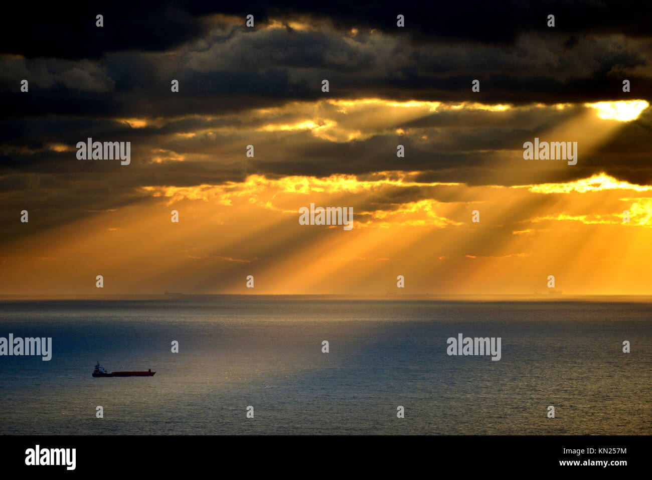 Container ship lit by rays of the setting sun, English channel. - Stock Image
