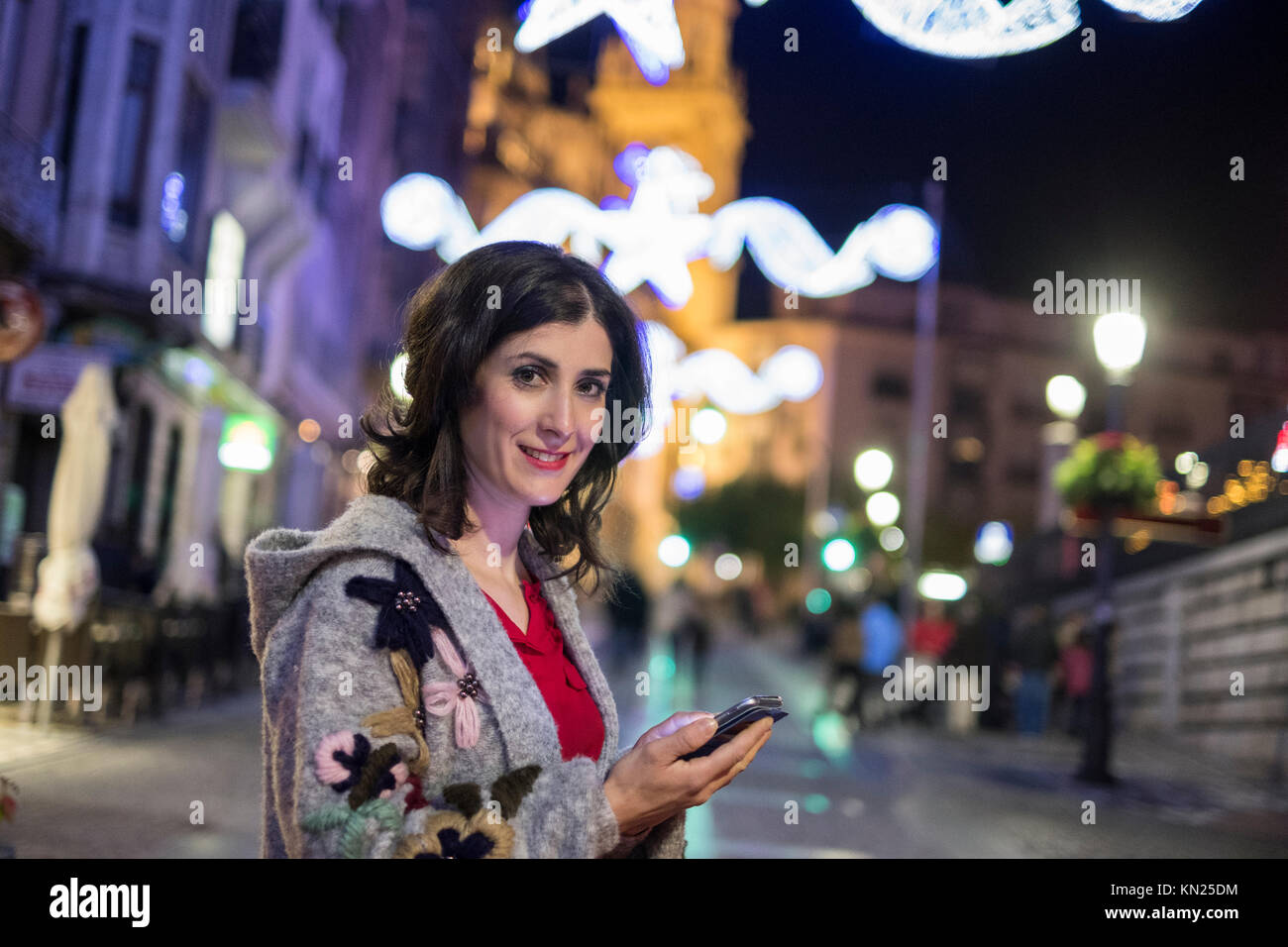 Woman sending and looking social network messages in winter christmas images in the city - Stock Image
