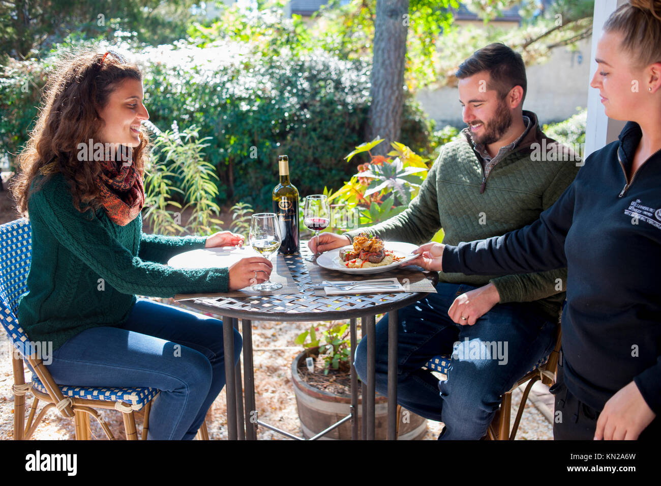 USA Virginia VA Williamsburg Winery dining restaurant wine vineyard food couple being served in the garden restaurant - Stock Image