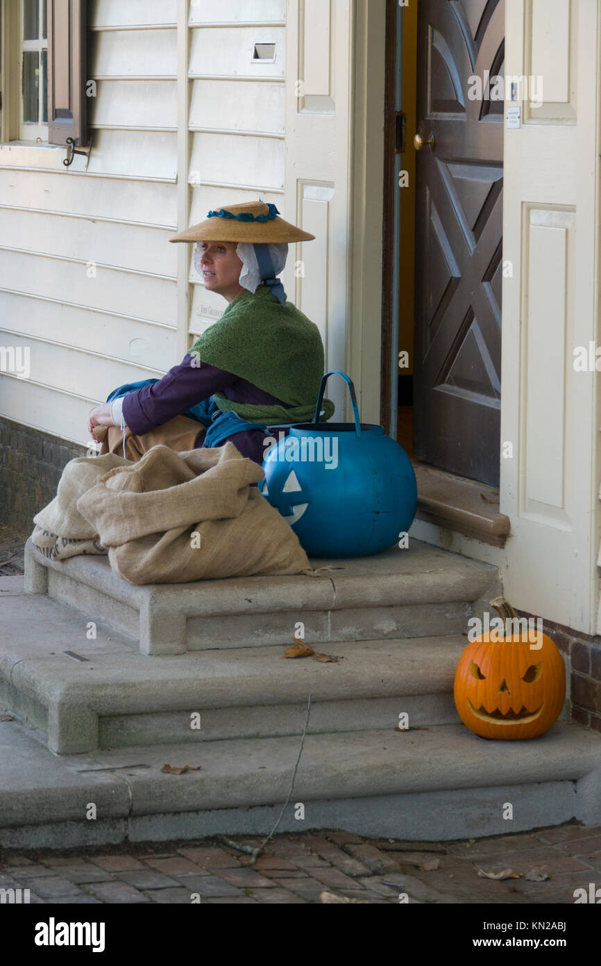 USA Virginia Colonial Williamsburg Autumn Fall Halloween carved pumpkins jack-o-lanterns woman docent interpreter - Stock Image