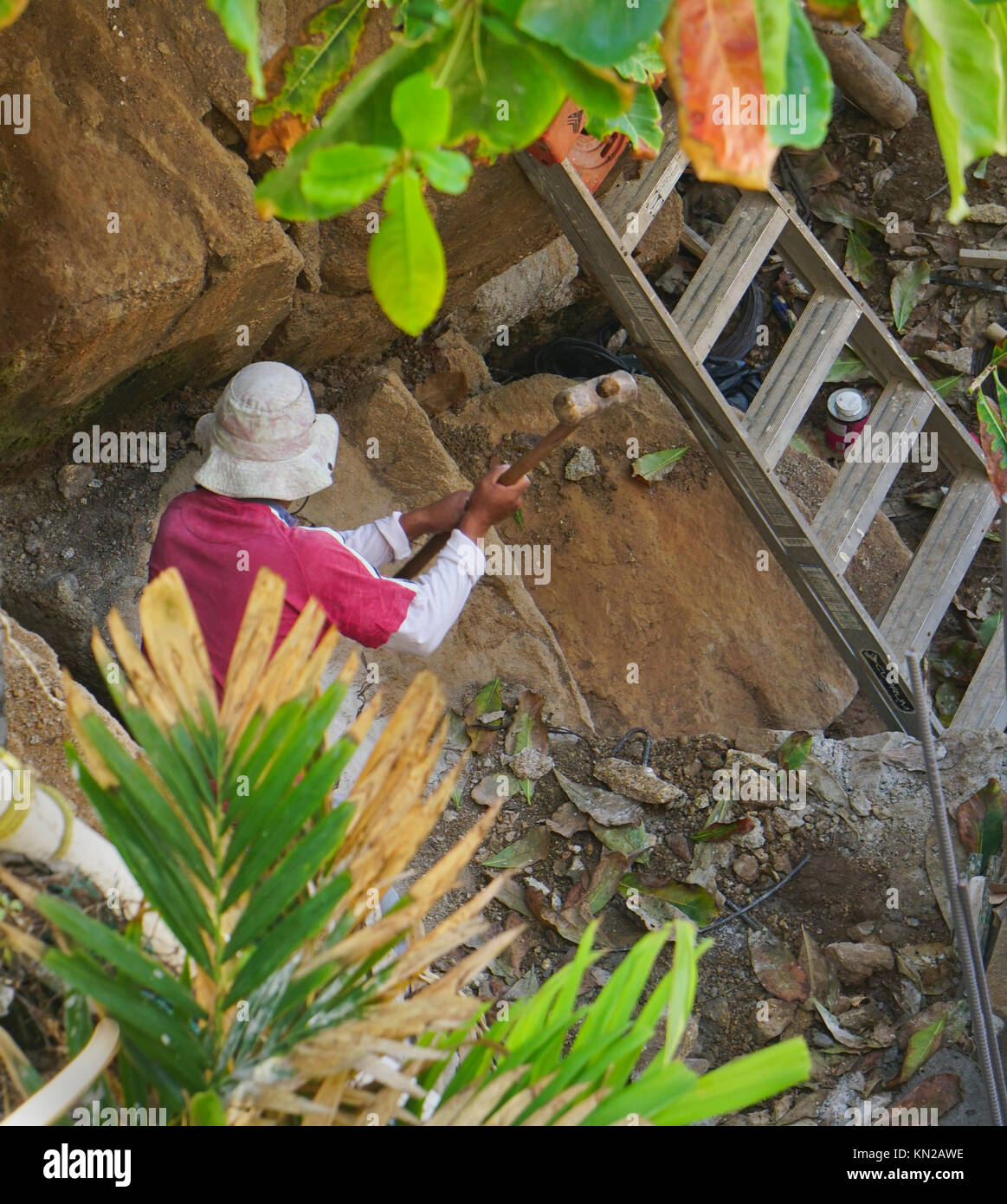 Mexican man hammering rocks to make base of pool in Acapulco, Mexico - Stock Image