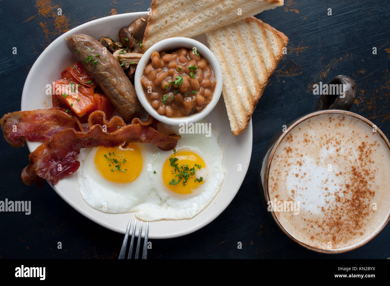 Food A classic Full English Breakfast of eggs bacon sausage or bangers beans mushrooms tomatoes and toast with coffee - Stock Image