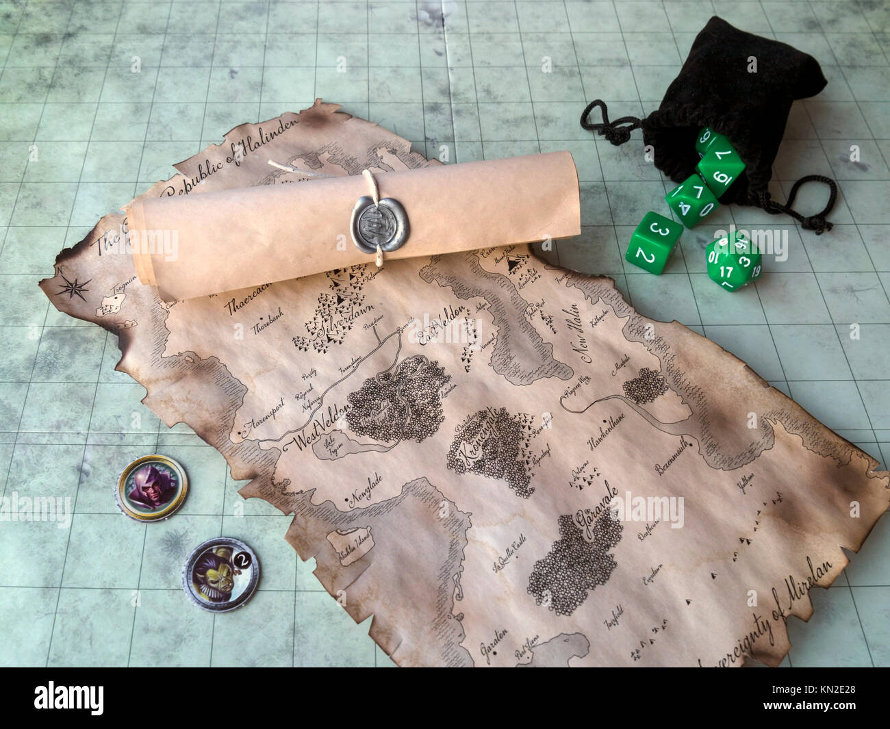 Fantasy roll playing game map with sealed scroll, dice and counters on game board - Stock Image