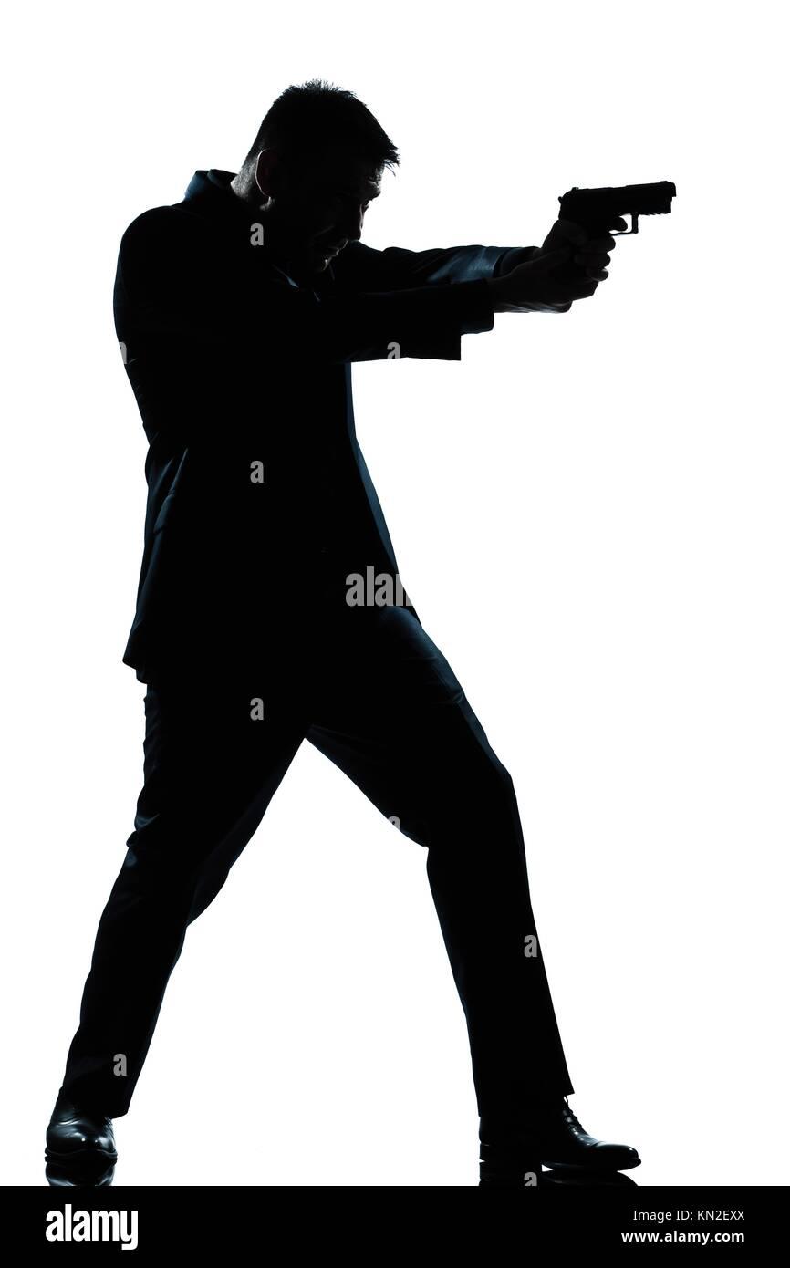 one caucasian spy criminal policeman detective man aiming shooting gun full length silhouette in studio isolated - Stock Image