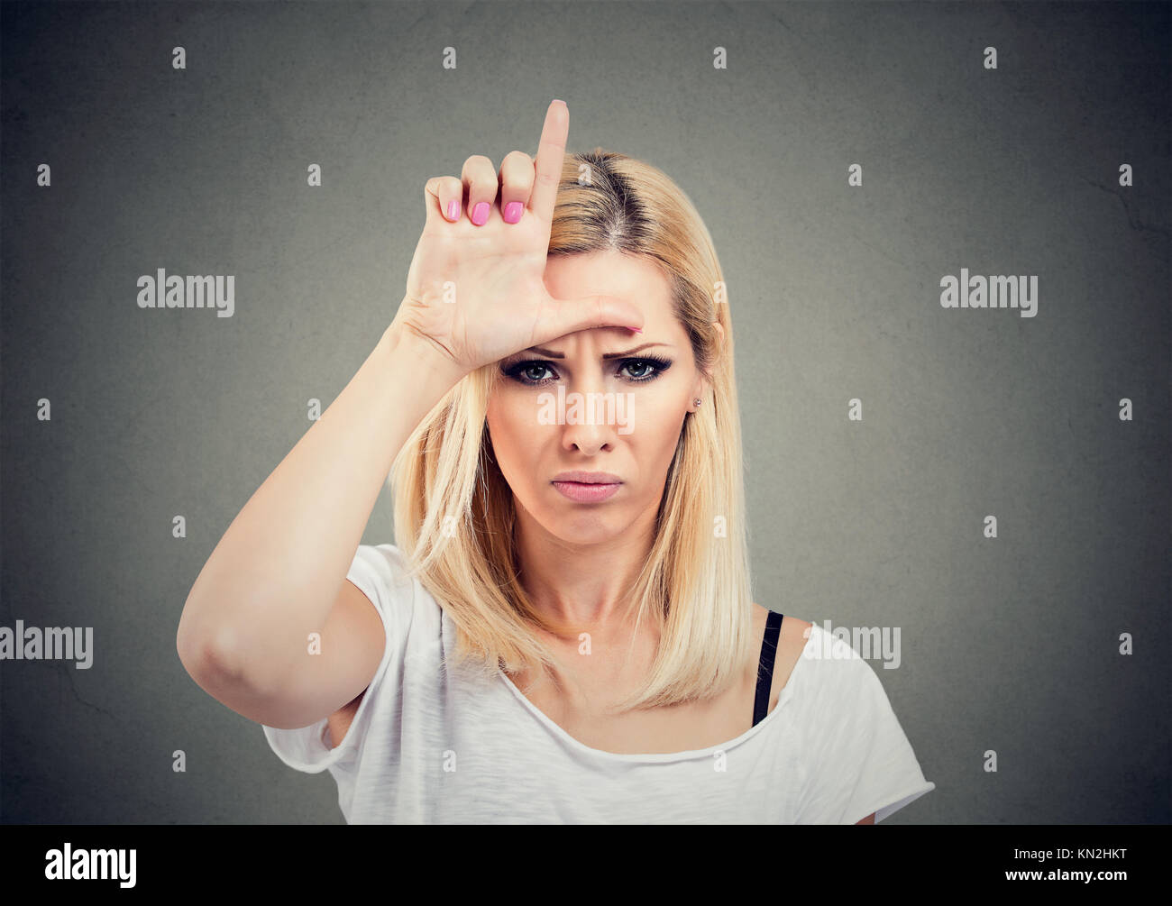 Closeup portrait unhappy woman giving loser sign on forehead, looking at you with anger and hatred on face isolated - Stock Image