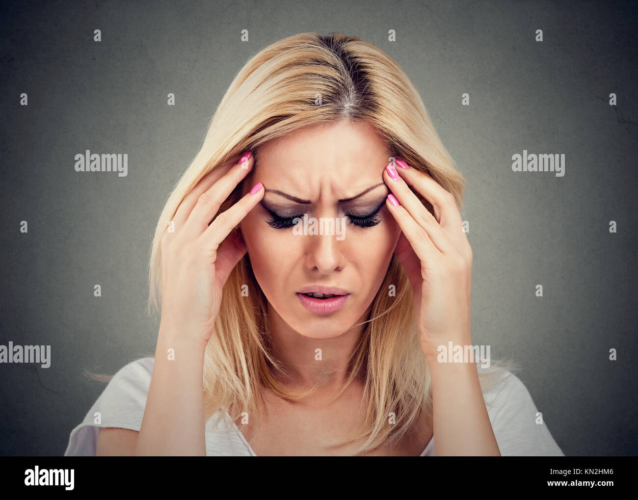 Closeup portrait sad woman with worried stressed face expression looking down - Stock Image