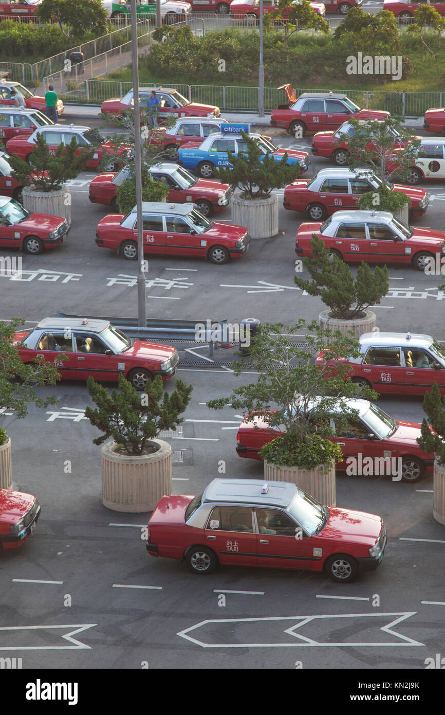 December 3, 2011: Hong Kong, rows of red taxis lined up outside the airport waiting for passengers - Stock Image